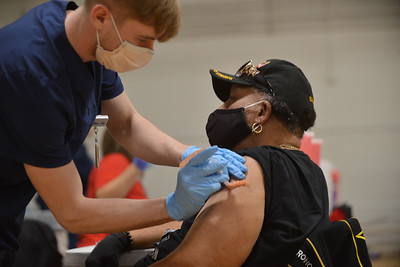 LPN Brice Headrick injects Eddie Haney, 74, who showed up at Linwood YMCA for his first COVID-19 vaccination on Feb. 3.