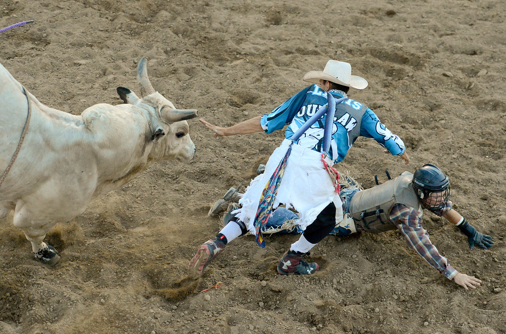 . LONGMONT, CO - AUGUST 5: Bullfighter Zane Lewis, of Torrington, Wyoming, tries to distract a bull from charging at rider Wyatt Noe, of Larkspur, during the rodeo at the Boulder County Fair on Aug. 5, 2018.  (Photo by Matthew Jonas/Staff Photographer)
