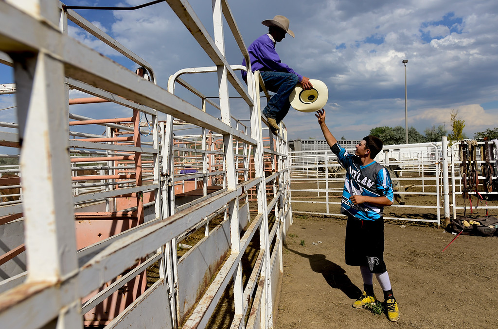 . LONGMONT, CO - AUGUST 5: From left: Wyatt Smith, of Byers, hands Bull Fighter Zane Lewis, of Torrington, Wyoming, his hat before the start of the rodeo at the Boulder County Fair on Aug. 5, 2018.  (Photo by Matthew Jonas/Staff Photographer)