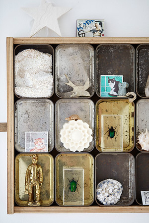 Collection of old storage tins with tiny animal ornaments in Birmingham home, England, UK