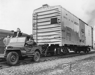 """2020.016.F.087--phil weibler collection 8x10 print--CRI&P--new aluminum boxcar 20060 (Mt Vernon Car Co) photo stunt--Chicago IL--1945 0000. """"The Rock Island Lines hasn't really started using Army jeeps to pull freight cars, but with the new light-weight aluminum alloy used in the construction of the car pictured above, it really can be done. Designed by the Reynolds Metals Company and built by the Mount Vernon (Illinois) Car Co., the first of ten new aluminum cars was recently deliverd to the Rock Island in Chicago, where it was viewed by thousands of railroaders and the public generally. (Including, of course, K.T. Stevens, beauteous star of stage and screen who took a ride in the jeep.) The special high tensile aluminum alloy of these cars was first developed by the Reynolds Company for B-29 bombers, and because of the lightness and low center of gravity of the cars, they can be used to advantage on high speed passenger as well as freight trains. They have the same capacity as the ordinary boxcar. The new equipment which transportation experts predict will contribute greatly to rail progress, was the result of months of technical study and experiment, and while material shortages will limit production for the present, the Reynolds Company is looking forward tro extensive post-war markets on railroads. Five of the cars which the Rock Island will acquire are equipped with high speed passenger trucks and roller bearings, and will be placed in service as soon as they are received, officials of the railroad said."""""""