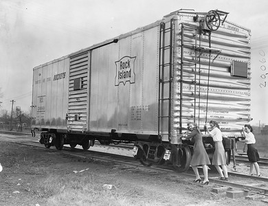"""2020.016.F.090--phil weibler collection 8x10 print--CRI&P--new aluminum boxcar 20060 (Mt Vernon Car Co) photo stunt--Chicago IL--1945 0000. """"The Rock Island Lines hasn't really started using Army jeeps to pull freight cars, but with the new light-weight aluminum alloy used in the construction of the car pictured above, it really can be done. Designed by the Reynolds Metals Company and built by the Mount Vernon (Illinois) Car Co., the first of ten new aluminum cars was recently deliverd to the Rock Island in Chicago, where it was viewed by thousands of railroaders and the public generally. (Including, of course, K.T. Stevens, beauteous star of stage and screen who took a ride in the jeep.) The special high tensile aluminum alloy of these cars was first developed by the Reynolds Company for B-29 bombers, and because of the lightness and low center of gravity of the cars, they can be used to advantage on high speed passenger as well as freight trains. They have the same capacity as the ordinary boxcar. The new equipment which transportation experts predict will contribute greatly to rail progress, was the result of months of technical study and experiment, and while material shortages will limit production for the present, the Reynolds Company is looking forward tro extensive post-war markets on railroads. Five of the cars which the Rock Island will acquire are equipped with high speed passenger trucks and roller bearings, and will be placed in service as soon as they are received, officials of the railroad said."""""""