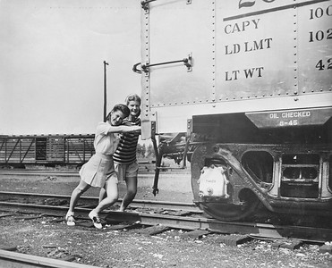 """2020.016.F.089--phil weibler collection 8x10 print--CRI&P--new aluminum boxcar 20060 (Mt Vernon Car Co) photo stunt--Chicago IL--1945 0000. """"The Rock Island Lines hasn't really started using Army jeeps to pull freight cars, but with the new light-weight aluminum alloy used in the construction of the car pictured above, it really can be done. Designed by the Reynolds Metals Company and built by the Mount Vernon (Illinois) Car Co., the first of ten new aluminum cars was recently deliverd to the Rock Island in Chicago, where it was viewed by thousands of railroaders and the public generally. (Including, of course, K.T. Stevens, beauteous star of stage and screen who took a ride in the jeep.) The special high tensile aluminum alloy of these cars was first developed by the Reynolds Company for B-29 bombers, and because of the lightness and low center of gravity of the cars, they can be used to advantage on high speed passenger as well as freight trains. They have the same capacity as the ordinary boxcar. The new equipment which transportation experts predict will contribute greatly to rail progress, was the result of months of technical study and experiment, and while material shortages will limit production for the present, the Reynolds Company is looking forward tro extensive post-war markets on railroads. Five of the cars which the Rock Island will acquire are equipped with high speed passenger trucks and roller bearings, and will be placed in service as soon as they are received, officials of the railroad said."""""""