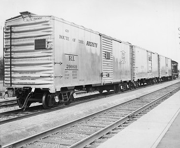 "2020.016.F.085--phil weibler collection 8x10 print--CRI&P--new aluminum boxcar 20060 (Mt Vernon Car Co)--Chicago IL--1945 0000. ""The Rock Island Lines hasn't really started using Army jeeps to pull freight cars, but with the new light-weight aluminum alloy used in the construction of the car pictured above, it really can be done. Designed by the Reynolds Metals Company and built by the Mount Vernon (Illinois) Car Co., the first of ten new aluminum cars was recently deliverd to the Rock Island in Chicago, where it was viewed by thousands of railroaders and the public generally. (Including, of course, K.T. Stevens, beauteous star of stage and screen who took a ride in the jeep.) The special high tensile aluminum alloy of these cars was first developed by the Reynolds Company for B-29 bombers, and because of the lightness and low center of gravity of the cars, they can be used to advantage on high speed passenger as well as freight trains. They have the same capacity as the ordinary boxcar. The new equipment which transportation experts predict will contribute greatly to rail progress, was the result of months of technical study and experiment, and while material shortages will limit production for the present, the Reynolds Company is looking forward tro extensive post-war markets on railroads. Five of the cars which the Rock Island will acquire are equipped with high speed passenger trucks and roller bearings, and will be placed in service as soon as they are received, officials of the railroad said."""