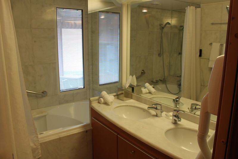 """I am 6' tall. Upon stepping (up) into  the tub/shower I was within 1"""" of the ceiling. You can see in the reflection that the top of the shower head is several inches below the ceiling. This causes anyone over (I'd say) 5""""6"""" to squat or hunch over to wash their hair."""