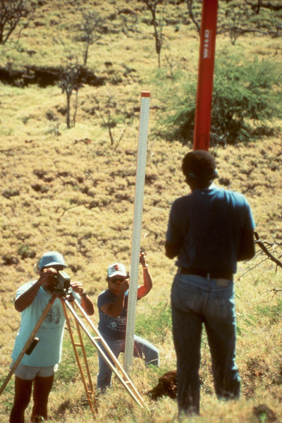Luther Sipison (Papua New Guinea) and Jack Sablan (Marianas Islands) assist Maurice Sako of HVO in a precise leveling survey of Puu Kohola heiau. Photo by Darcy Bevens.