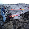 UH Hilo student Steve Clegg, wearing protective clothing, samples molten lava from a pahoehoe flow of Kilauea volcano. Photo by UH Hilo.
