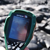 A radiometer, held by a UH Hilo Geology student, indicates a temperature of 270 degrees centigrade on a cooling lava flow on Kilauea. Photo by Drew Lubiniecki.