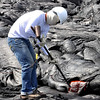 UH Hilo Geology student Bryan Patterson inserts a thermocouple wire into a lava flow, while an assistant reads the temperature in a cooler area. Bryan is wearing sunglasses and a face mask, as well as regular protective clothing, because of the heat. This is part of the field work done by students in Ken Hon's Volcanology class. Photo by Steve Lundblad.