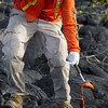 UH Hilo student collects a sample of molten pahoehoe lava; note protective gear. Photo by Jack Dykinga.