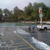 At the Keauhou Boat Harbor in Kona, a fisherman is surprised to find himself knee-deep in water as a wave from the 2009 tsunami washes into the parking lot; the same tsunami created huge and deadly waves in Samoa.