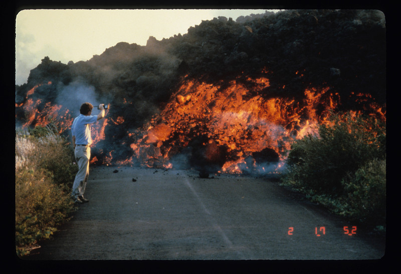 Scientist Robert Decker shields his face against the heat of a Kilauea aa flow from Puu Oo in 1983, as he monitors its progress along a road. Photo by Jim Griggs, USGS HVO.