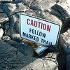 "Lava engulfed the post of this ""Caution Follow Marked Trail"" sign, but the upper sign is intact. Photo by CSAV."