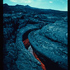 During the 1984 eruption of Mauna Loa, lava is seen flowing within a partially drained channel. Photo by M.L. Summers, USGS.