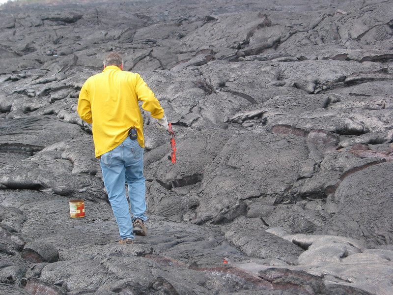 A scientist carries a sample of molten lava towards a coffee can filled with water in order to quench the sample quickly; note protective clothing. Photo by Darcy Bevens.