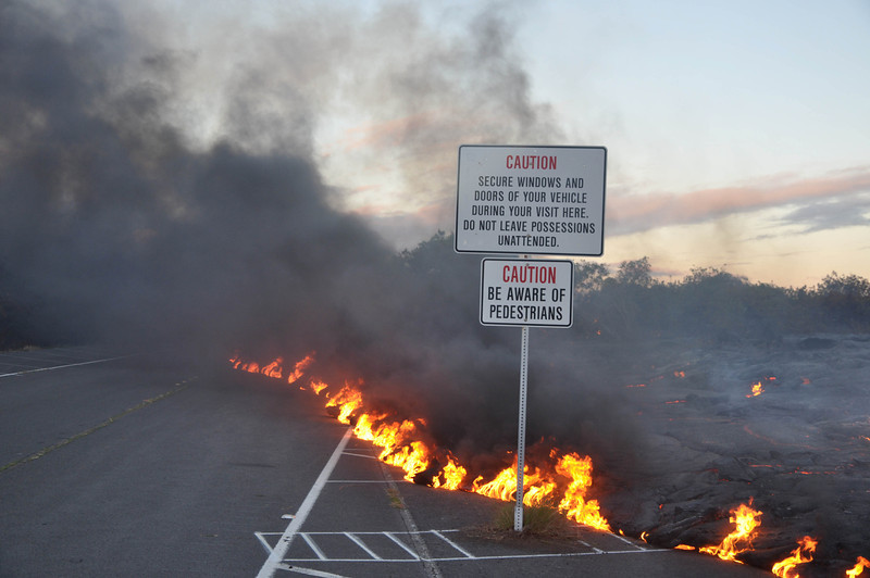 A lava flow in Kalapana crosses the road and heads towards safety signs; note the fume from the burning asphalt. Photo by Darcy Bevens.