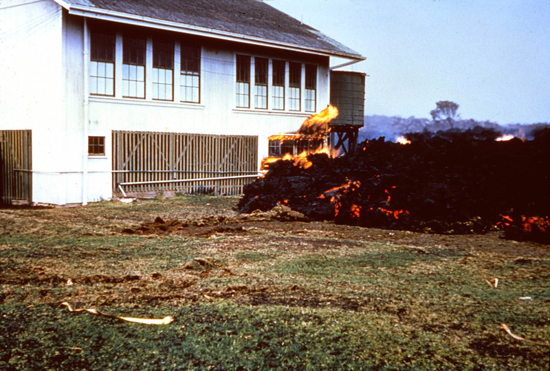 An aa flow begins to burn the schoolhouse at Kapoho, Hawaii in 1960.