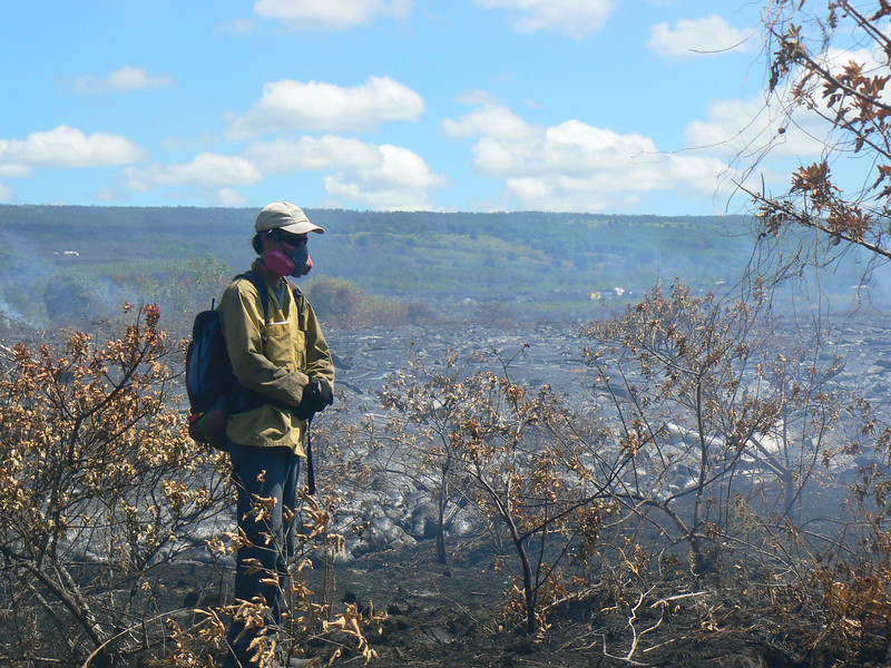 Matt Patrick of USGS HVO wears a respirator (gas mask) while mapping the flow field at Kalapana; note protective clothing. Photo by CSAV.
