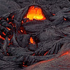 Black crust of a solidifying  pahoehoe flow is lifted up, revealing molten lava beneath. Photo by Steve Lundblad.