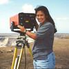 UH Hilo geology student Francine Coloma demonstrates an EDM (Electronic Distance Measurement) instrument above Kilauea Caldera. Photo by CSAV.