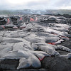 Pahoehoe lava drops down an incline and then begins to fill a shallow area near Kalapana. Photo by Darcy Bevens.