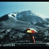 In this view from the NE, a scientist uses EDM to measure deformation at Mount St. Helens, particularly the bulge that is rising at a rate of five feet per day as magma pushes up. Photo by Peter Lipman, USGS, 27 April 1980.