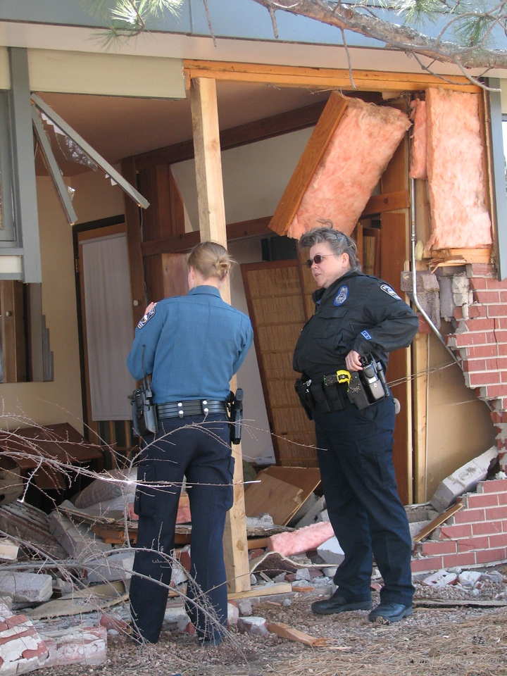 CSPD Officers Huffman and Patricia look over the damaged house.