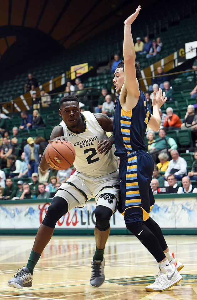 Colorado State University's #2 Emmanuel Omogbo takes the ball down court past Fort Lewis' #11 Kane Martinez during their game Wednesday, Nov. 16, 2016, at Moby Arena in Fort Collins. (Photo by Jenny Sparks/Loveland Reporter-Herald)