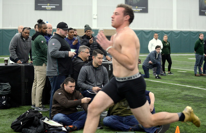 Football scouts crowd together with their stop watches as K.J. Carta-Samuels crosses the finish line of the 40-yard dash at Wednesday's pro day at Colorado State. (Mike Brohard/Loveland Reporter-Herald)