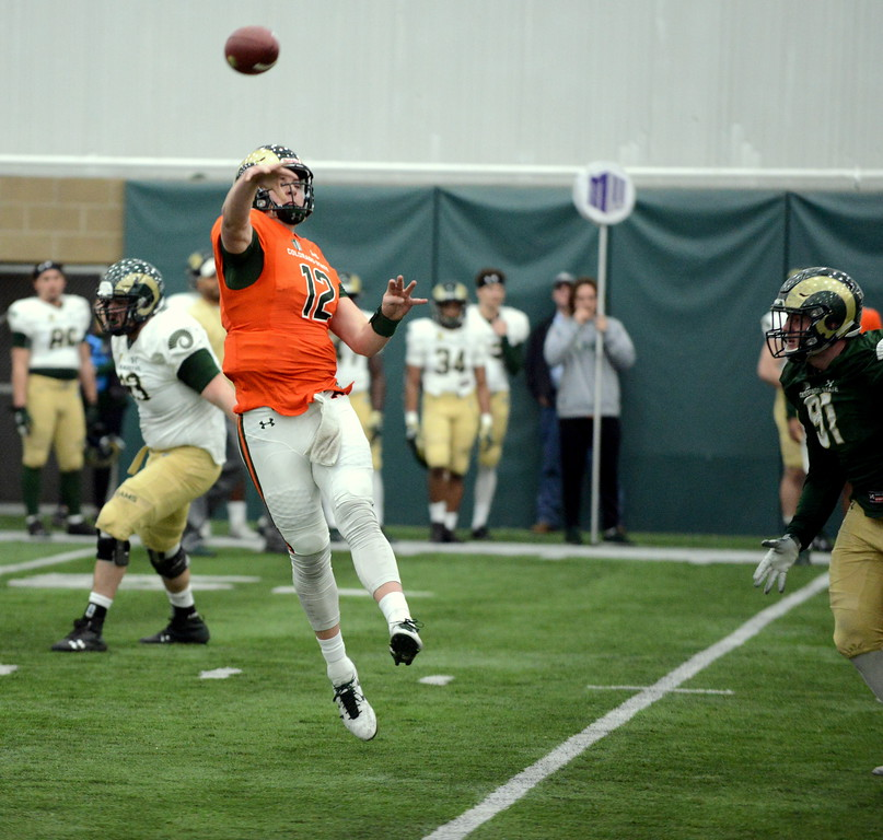 . Colorado State quarterback Patrick O\'Brien throws a pass after scrambling away from pressure during Thursday\'s scimmage at the indoor practice facility. (Mike Brohard/Loveland Reporter-Herald)
