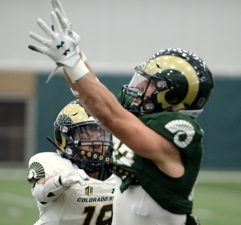 . Colorado State receiver Brenden Fulton reaches out to catch a pass as Xavier Goldsmith defends during Thursday\'s scimmage at the indoor practice facility. (Mike Brohard/Loveland Reporter-Herald)