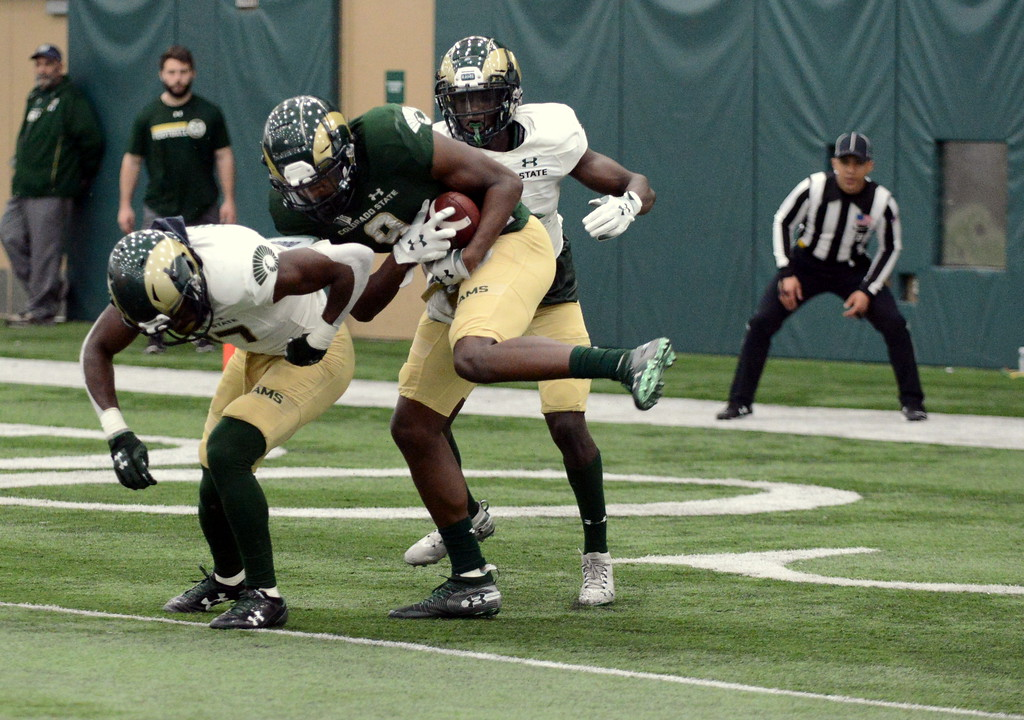 . Colorado State receiver Warren Jackson (9) hauls in a touchdown pass from Collin Hill against the defense of Logan Stewart (37) and Rashad Ajayi during Thursday\'s scrimmage at the indoor practice facility. (Mike Brohard/Loveland Reporter-Herald)