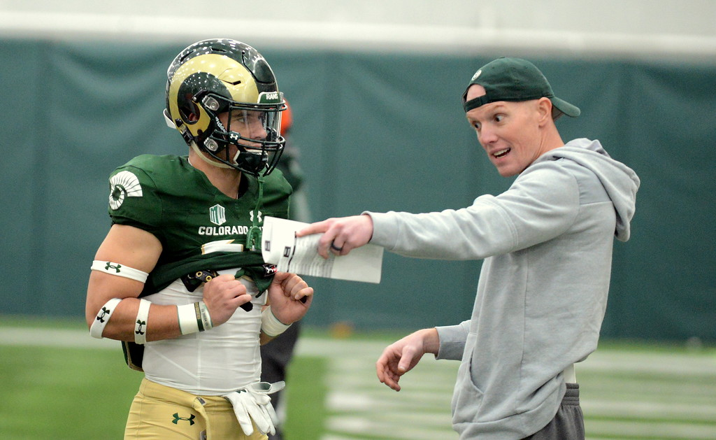 . Colorado State wide receivers coach Joe Cox discusses technique with Brenden Fulton before the start of Thursday\'s scimmage at the indoor practice facility. (Mike Brohard/Loveland Reporter-Herald)