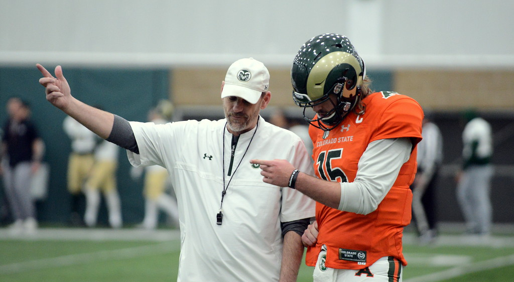 . Colorado State head coach Mike Bobo and quarterback Collin Hill discuss a scoring series during Thursday\'s scimmage at the indoor practice facility. (Mike Brohard/Loveland Reporter-Herald)