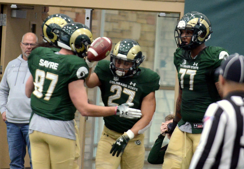 . Colorado State running back Jaylen Thomas is congratulated by teammates after his touchdown run during Thursday\'s scimmage at the indoor practice facility. (Mike Brohard/Loveland Reporter-Herald)