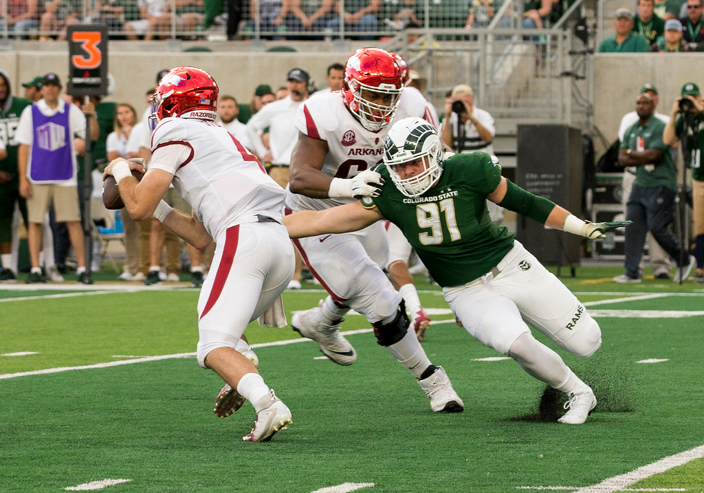 . Colorado State defensive lineman Jan-Phillip Bombek (91) gets a hand on Arkansas quarterback Ty Storey (4) as offensive lineman Brian Wallace (60) shoves him to the ground Saturday evening Sept., 8, 2018 at Canvas Stadium in Fort Collins. (Michael Brian/For the Reporter-Herald)