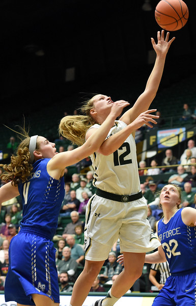 Colorado State's (12) Callie Kaiser attempts a shot as Air Force's (11) Cortney Porter throws out an arm to disrupt it during their game on Wednesday, Feb. 7, 2018 at Moby Arena in Fort Collins. Photo by Thieng Mai/Loveland Reporter-Herald.