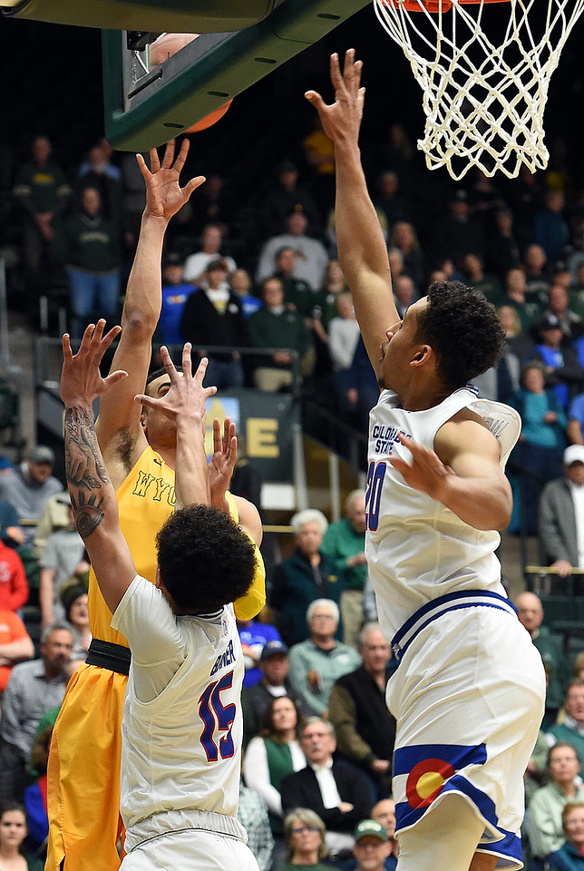 Colorado State University's (20) Deion James and (15) Anthony Bonner try to block a shot by Wyoming's (1) Justin James during their game Wednesday, Jan. 31, 2018, at Moby Arena in Fort Collins. (Photo by Jenny Sparks/Loveland Reporter-Herald)