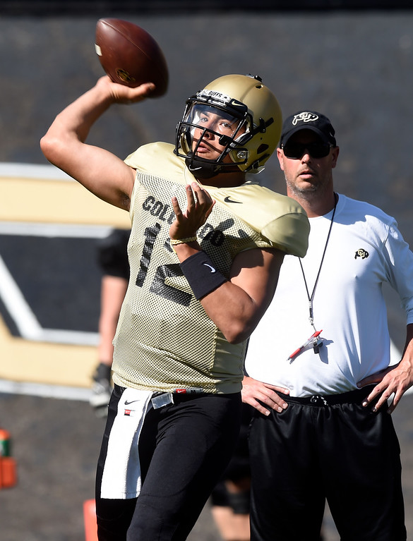 . Boulder, CO - AUGUST 11:  Steven Montez throws as Kurt Roper watches during the University of Colorado football scrimmage on August 11, 2018.(Photo by Cliff Grassmick/Staff Photographer)