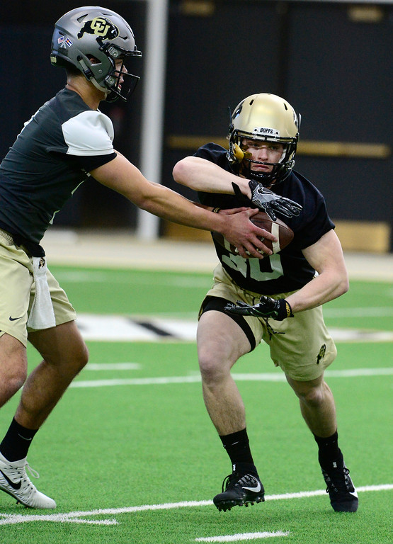 . University of Colorado\'s quarterback Tyer Lytle hands the ball off to tailback Andrew Wilk during practice on the CU Boulder Campus on Friday. For more photos go to buffzone.com Paul Aiken Staff Photographer Feb 23 2018
