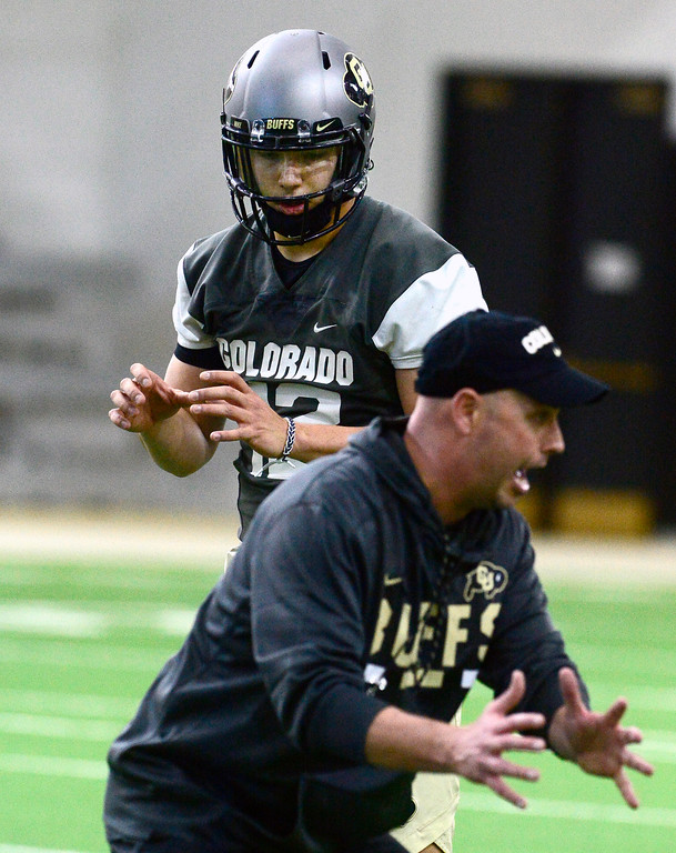 . University of Colorado\'s quarterback Steven Montez works with assistant coach Kurt Roper during practice on the CU Boulder Campus on Friday. For more photos go to buffzone.com Paul Aiken Staff Photographer Feb 23 2018