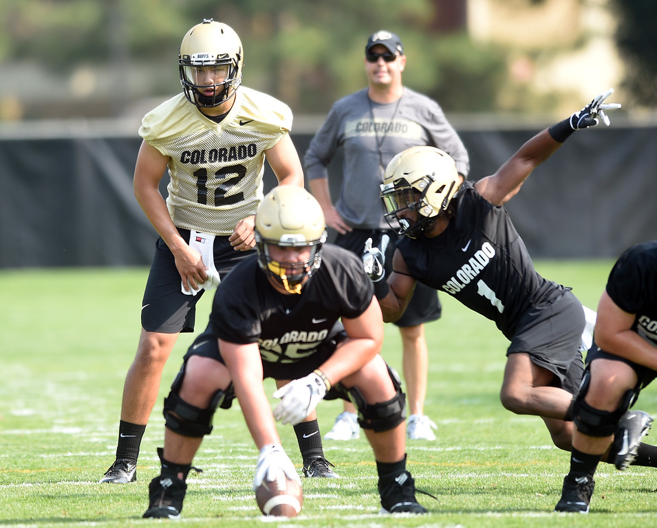 . Steven Montez with Donovan Lee in motion during CU Buffalo football practice on August 2, 2018. For more photos, go to buffzone.com. Cliff Grassmick  Staff Photographer  August 2, 2018