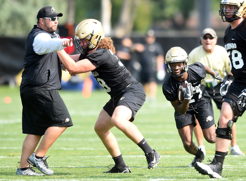 . Dylan Thomas on the run uses the block of Brady Russell on coach Klayton Adams during CU Buffalo football practice on August 2, 2018. For more photos, go to buffzone.com. Cliff Grassmick  Staff Photographer  August 2, 2018