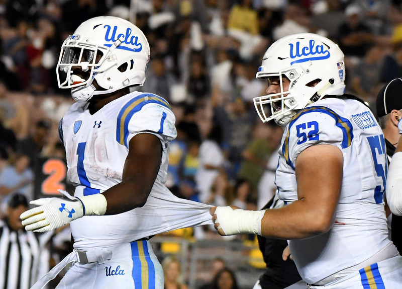 UCLA Bruins running back Soso Jamabo (1) reacts as teammate offensive lineman Scott Quessenberry (52) pulls his jersey after running for a touchdown against the Colorado Buffaloes in the second half of a NCAA college football game at the Rose Bowl in Pasadena, Calif., Saturday, Sept. 30, 2017. UCLA Bruins won 27-23. (Photo by Keith Birmingham, Pasadena Star-News/SCNG)