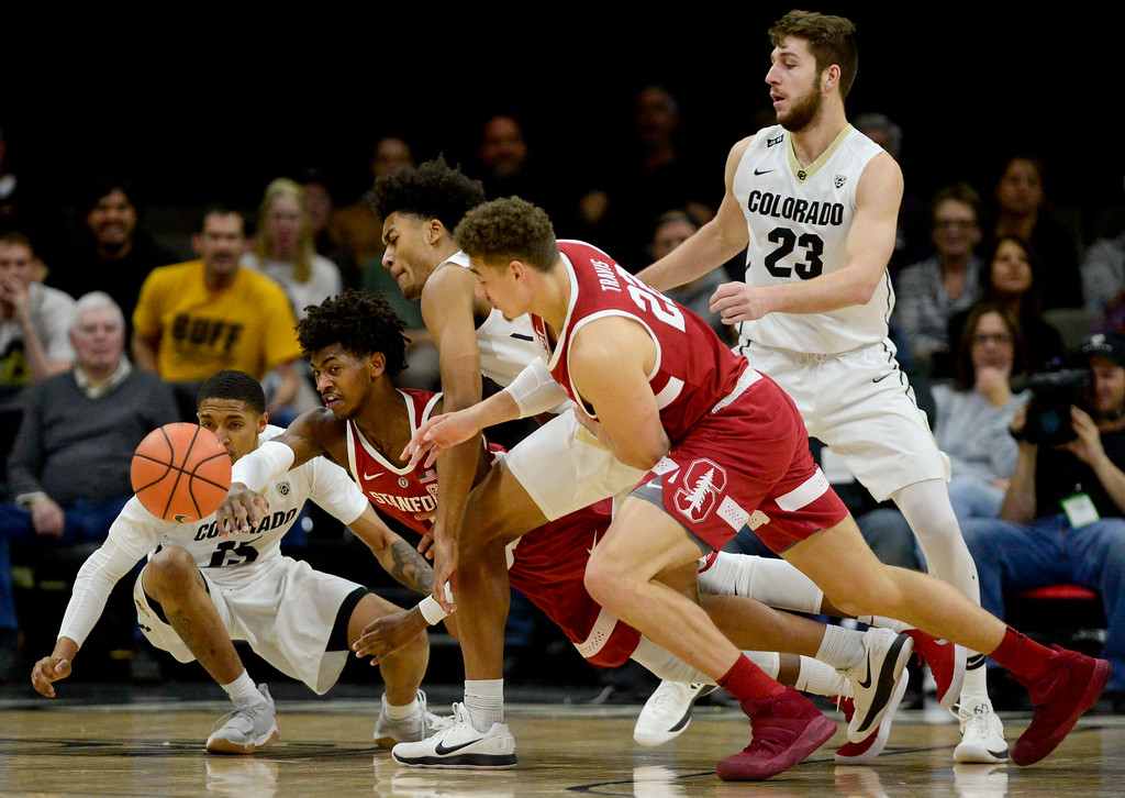 . University of Colorado\'s Dominique Collier (No. 15) and D\'Shawn Schwartz (No. 0) battle for a loose ball with Stanford\'s Daejon Davis (No. 1) and Reid Travis (No. 22) at the Coors Event Center in Boulder, Colorado on Feb. 11, 2018. (Photo by Matthew Jonas/Staff Photographer)