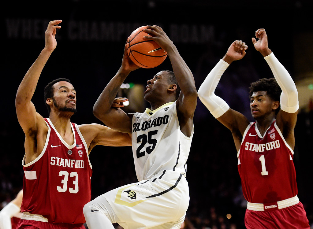 . University of Colorado\'s McKinley Wright (No. 25) puts up a shot between Stanford\'s Trevor Stanback (No. 33) and Deacon Davis (No. 1) at the Coors Event Center in Boulder, Colorado on Feb. 11, 2018. (Photo by Matthew Jonas/Staff Photographer)