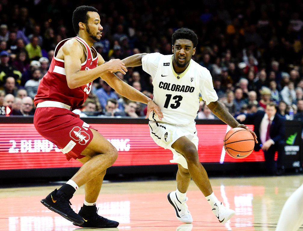 . University of Colorado\'s Namon Wright (No. 13) drives around Stanford\'s Trevor Stanback (No. 33) at the Coors Event Center in Boulder, Colorado on Feb. 11, 2018. (Photo by Matthew Jonas/Staff Photographer)