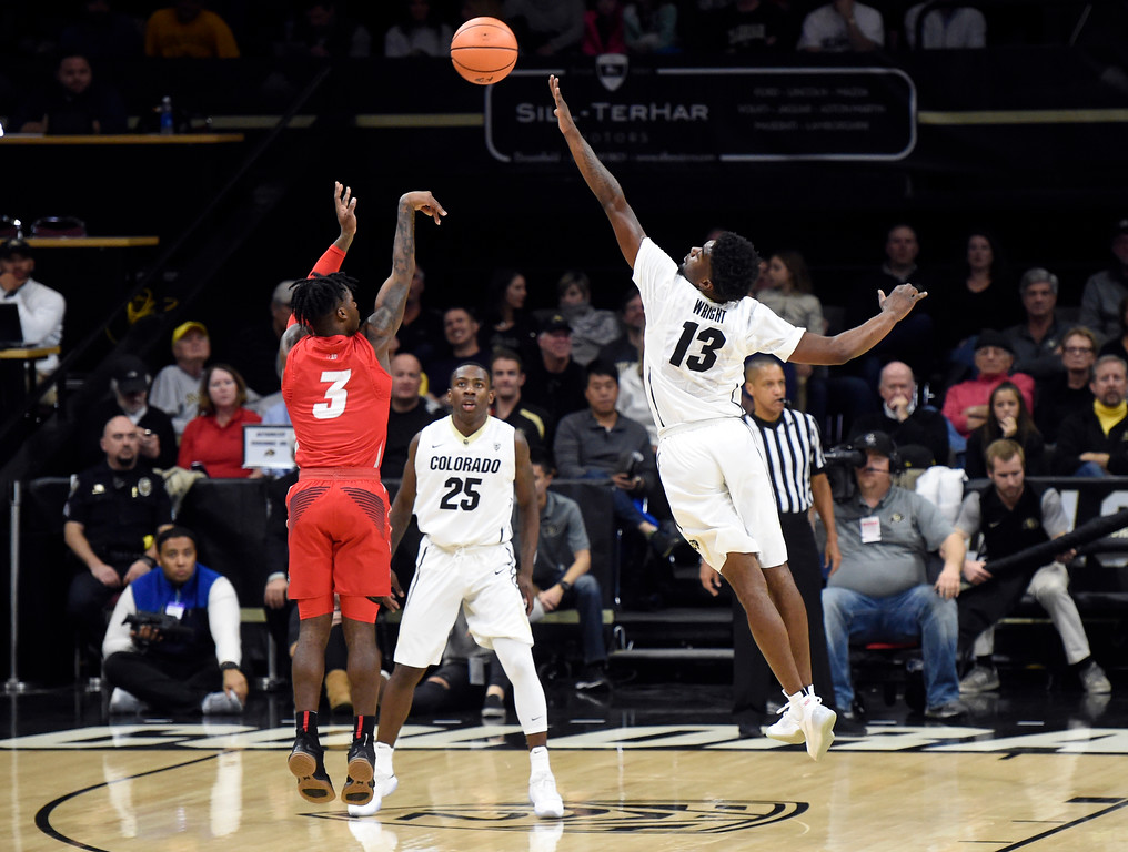 . University of Colorado\'s Nomon Wright tries to block the shot of Antino Jackson during a NCAA game against New Mexico on Wednesay at the Coors Event Center in Boulder. More photos: www.Buffzone.com Jeremy Papasso/ Staff Photographer 12/06/2017