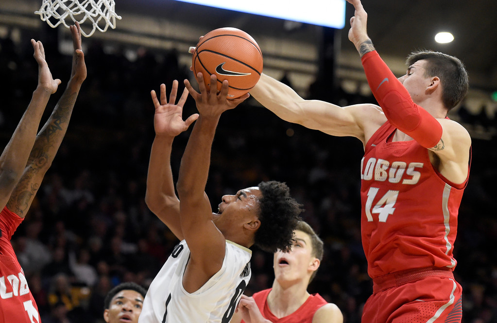 . University of Colorado\'s D\'Shawn Schwartz gets his shot blocked by Dane Kuiper during a NCAA game against New Mexico on Wednesay at the Coors Event Center in Boulder. More photos: www.Buffzone.com Jeremy Papasso/ Staff Photographer 12/06/2017