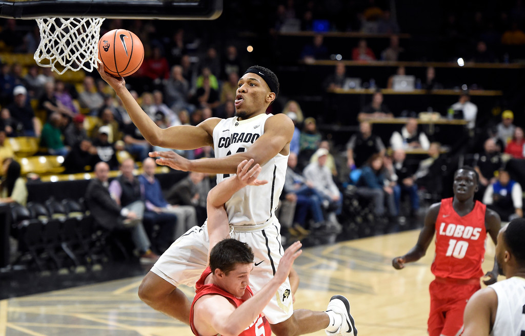 . University of Colorado\'s George King goes for a layup over  Joe Furstinger during a NCAA game against New Mexico on Wednesay at the Coors Event Center in Boulder. More photos: www.Buffzone.com Jeremy Papasso/ Staff Photographer 12/06/2017
